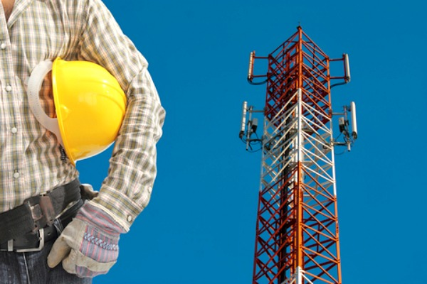 cell-tower-worker-with-yellow-hardhat